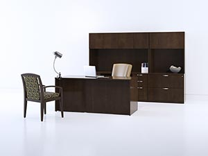 Bow Top Desk sits in front of storage wall shown in Shaker Cherry laminate with Soft edge and Axis pulls