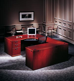 Single Pedestal CRT Desk Left with Bow Top, Executive Bridge Top and Modesty Panel, Single Pedestal Credenza shown in Light Cherry.